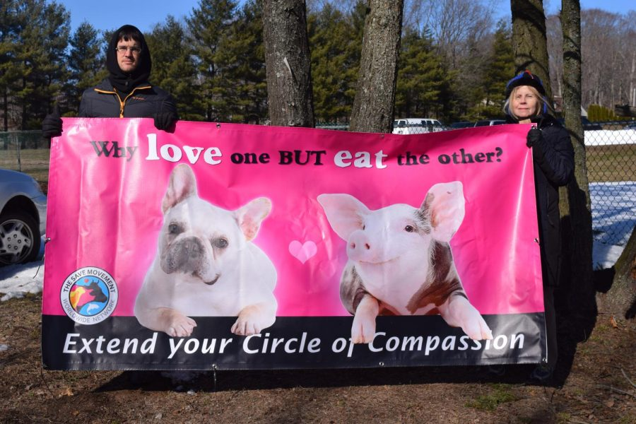 Activists David Herpst and Karen stand behind a animal equality sign