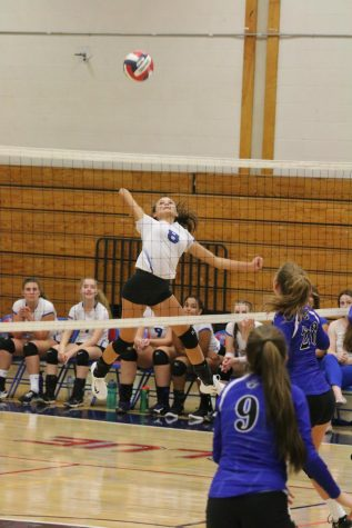 Junior Sydney Fowler leaps for a spike